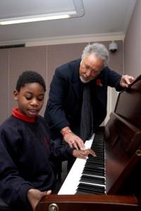 Sir Tom Jones walesi énekes és egy zongorázó kisfiúval a Nordoff Robbins Zeneiskolában Londonban 2010. november 18-án