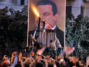 Tüntetők letépik Hoszni Mubarak egyiptomi elnök portréját az egyiptomi Alexandriában 2011. január 25-én