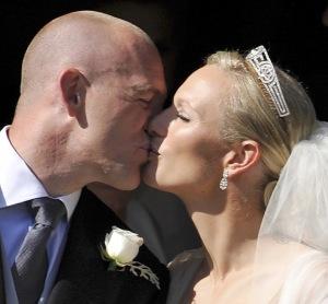 Zara Phillips, II. Erzsébet brit királynő unokája és Mike Tindall angol rögbisztárral megcsókolják egymást az esküvőjük után a skóciai Edinburghben 2011. július 30-án