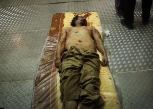 Moammer el-Kadhafi líbiai vezető holtteste egy miszrátai hullaházban 2011. október 21-én, egy nappal az után, hogy a líbiai polgárháború forradalmárai elfogták és megölték.