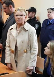 Julija Timosenko volt ukrán miniszterelnök a lánya kezét fogja a vádlottak padján egy kijevi bíróságon 2011. október 11-én