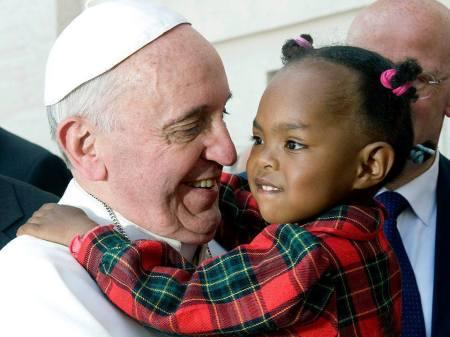 Ferenc pápa egy kislánnyal a karján a pápai vasútállomáson 2013. június 23-án