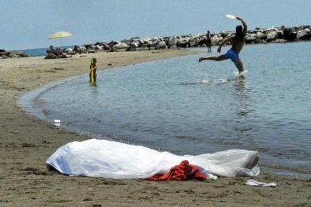 Játszanak egy holttest mellett az olaszországi Forima strandján 2013. június 17-én