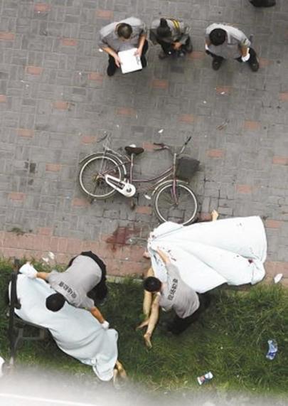 Ablakban szexelő pár holttestét takarják le a kínai Wuhanban 2013. június 28-án