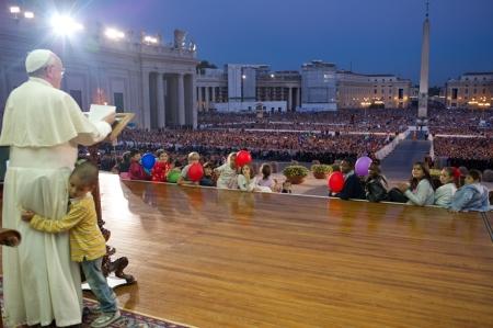 Ferenc pápa lábát karolja egy kisgyermek a vatikáni Szent Péter-téren 2013. október 27-én
