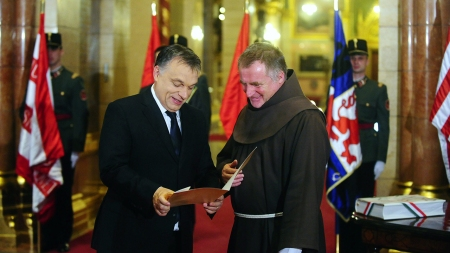 Orbán Viktor miniszterelnök és Böjte Csaba ferences rendi szerzetes, miután a pap letette a magyar állampolgársági eskütételét az Országházban 2013. december 5-én