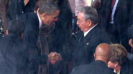 Barack Obama amerikai elnök kezet fog Raúl Castro kubai elnöknek Nelson Mandela Nobel-békedíjas dél-afrikai elnök gyászszertartásán Johannesburgban 2013. december 10-én