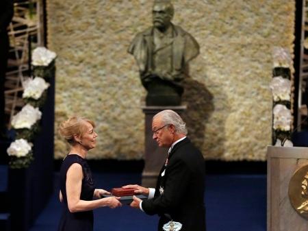 XVI. Károly Gusztáv svéd király átadja az irodalmi Nobel-díjat Alice Munro kanadai írónő lányának, Jennynek Stockholmban 2013. december 10-én