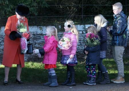 II. Erzsébet brit királynő virágot vesz át a Szent Mária Magdolna templomnál az angliai Sandringhamban 2013. december 25-én
